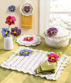 Pansy Kitchen Set Crochet PatternCelebrate the season in your kitchen with this delightful design featuring spring flowers. The Pansy Kitchen Set Crochet Pattern gives your kitchen a splash of bright color with a clean linen look. The pattern set includes Towel Topper, Potholder, Napkin Ring, Vase and Flowers, Placemat, Casserole Cover and Fridgie. All pi