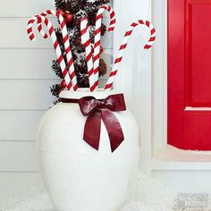 Take inspiration from classic Christmas candy and fill a white planter with decorative candy canes for a unique outdoor holiday decorating idea. Store-bought plastic canes and weather-treated ribbon mean this front door decor can last throughout the season.
