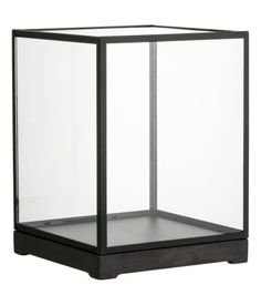 Large glass display case with a metal frame and clear glass sides. Mounted on an antique-finish wooden base. Size 8 1/4 x 8 1/4 x 11 in. @ H&M $34.99.