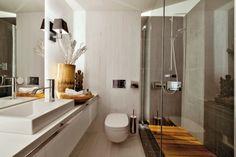 Koupelna je netradičně obložená bíle lakovaným dubovým dřevem. Je vybavena nábytkem na míru a umyvadlem Catalano. Pouze sprchový kout je obložený černým velkoformátovým obkladem. Rohož je z týkového dřeva, které barevně ladí s dřevěnou miskou, indickou soškou a vázou zhotovenou z kmene kokosové palmy