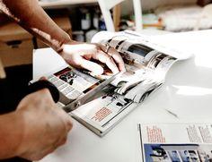 Gefaltete Seiten eines IKEA Katalogs werden mit einer Schere in Streifen geschnitten.