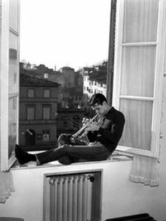 American jazz musician Chet Baker playing trumpet on a window ledge in Lucca 1961. (Photo by Archivio Cameraphoto Epoche/Getty Images)  Jan 1961