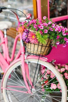 Pink cruiser bike with a basket of flowers.  #bicycles #cycling
