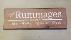"""Personalized Custom Family Name First Names House Sign Established by Walnut Routed Wood (6"""" x 20""""). Made of roughcut walnut planed smooth and cut to approximately 6-7"""" x 19-22"""" x 3/4"""" depending on the number of letters required for the sign. Decorative edge routing painted black and lettered routing painted white. Three keyhole slots routed in the back for multiple hanging options (nails not included). Sanded smooth and left natural (as in the first photo) or request an upgraded…"""