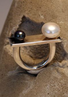 a simple but beautiful design with a small black and large white pearls/ sterling silver ring.