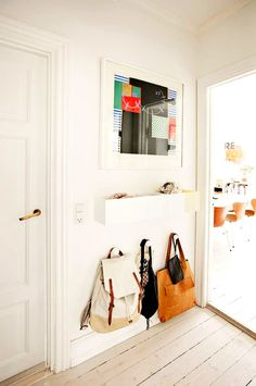 White walls, graphic wall art, wall hooks, and wall storage
