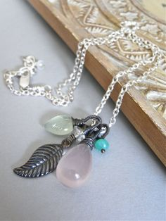 The Blossom necklace - a gorgeous smooth rose quartz, a carved prehnite leaf, a teensy chrysoprase rondelle, and a rock crystal quartz and sterling leaf combination have been carefully wirewrapped and added to bright sterling chain in this design.
