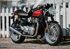 The 1200 Thruxton Classic Vintage by in front of a picket fence