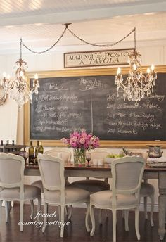 Dining room with two crystal chandeliers, large chalkboard and French-style…@lampsplus