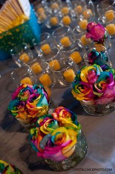 Centerpieces of rainbow roses. just to warn you, these can be temperamental and rot easily because of all the dye.