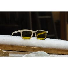 One of our first sunglasses ever produced, laying in the snow  uptitude, eyewear from recycled snowboards