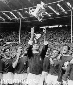 Manchester United's Noel Cantwell (c) throws the FA Cup into the air, watched by astonished teammates (l-r) Tony Dunne, Bobby Charlton, Pat Crerand, Albert Quixall and David Herd. Soccer - FA Cup - Final - Manchester United v Leicester City. 25th May 1963
