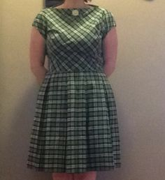 Vintage green plaid dress in excellent condition. Marked a  size 16 dress measures 38 inches in bust and 30 inches in the waist and 34 inches in length. Daisy pin on front has been with the dress since I purchased it many years ago and will come with the dress.  There are belt loops but no belt. $55