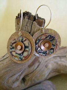 https://flic.kr/p/5itWXi | Riveted Earrings | Disks of textured & plain brass sheet, domed on a dapping block, then torched for a lucious weathered patina. Painted & powdered a stamped piece of clay, then riveted all the pieces together with GF wire.  So much fun!  While I'm a big fan of these half-loop earwires, my next goal is to work on custom earwires that compliment the design.