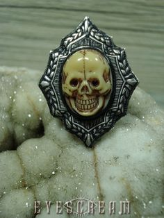 DESIGN:  * Gothic Dark Macabre Ornate Deco Diamond Skull Ring sz 8 by Eyescream.    COLOR:   * Silver, Black, Beige/Cream, Blood Red, Dark Umber details.    MATERIALS:  * Black Epoxy, Vintage Glass Skull, Blood Red Swarovski crystal eyes, antiqued silverplated over brass diamond Deco frame design...