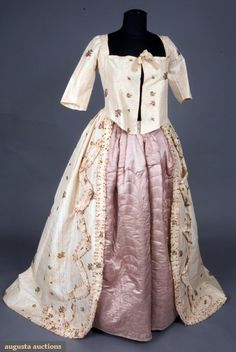 FLORAL SILK BROCADE ROBE A L'ANGLAISE, 1780s. Cream silk taffeta woven with textured stripes and brocaded with widely scattered red, pink and purple floral sprays and sprigs, square neckline and edge to edge front closure, elbow length fitted untrimmed sleeves, waist with front and back rounded point, open front skirt with fly-fringe edged ruched silk applied in zig-zag pattern, skirt knife pleated to bodice back and sides, homespun linen bodice & sleeve lining.