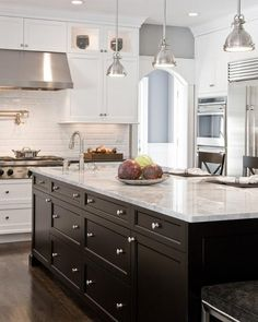 Large Island with large drawers, white perimeter cabinetry, dark wood floors #kitchen