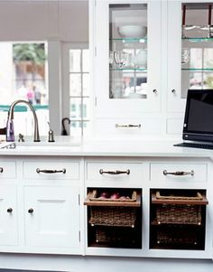 Glass-fronted cabinets, open on two sides, hold crystal and china from Wedgwood. Polished nickel hardware feels substantial to the touch and gleams against the Scullery White paint, by Christopher Peacock Paint, on the cabinets.