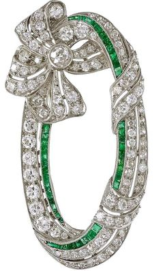 Art Deco Emerald Diamond Platinum Ribbon Brooch. A striking Art Deco Emerald and Diamond Platinum Oval Ribbon Brooch. This Art Deco Brooch has 105 Old mine cut Diamonds of H-I color VS/SI with a total weight of 5.75cts with 44 caliber-cut Emeralds approximately 1.10 cts. total weight. Circa 1925