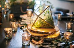 For a more modern look, add a neat terrarium centerpiece filled with greenery. The little lights in this example add a dreamy glow to this rustic tablescape.