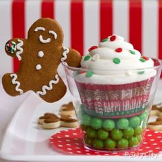 Let a gingerbread boy lend an arm to cups of good cheer filled with candy and a cupcake! Click the pic for more merry Christmas desserts.