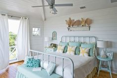 Beautiful white and light ocean blue bedroom from Coastal Living Magazine - Love the fans on the antiqued shelf.