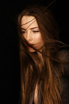 Dark brown hair blowing in the wind.