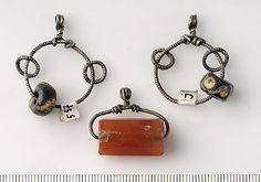 """Birka, grave 557. """"silver, glas, karneol: 2 hängen: 2 små ringar och glaspärla uppträdda på större ring; 1 hänge: avlång facetterad karneolpärla uppträdd på silverring. Ringar gjordes av räfflad silvertråd. """" Viking age / Silver and pearl pendants/ Uppland"""