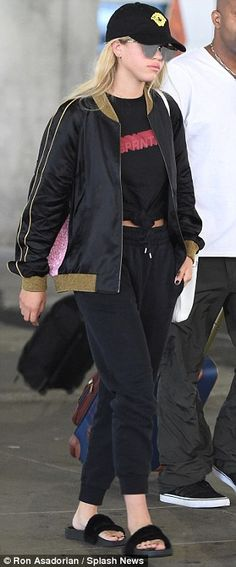 Dressed down: Sofia kept comfortable for her journey in her T-shirt, sweatpants, jacket and slip-on sandals