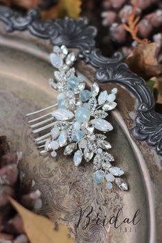 Свадебный гребень украшен прозрачными и опаловыми кристаллами, несмотря на легкость и нежность изделия, в прическе оно сидит надежно и комфортно. Цвет основы - проволока (золотого или серебристого цветов), кристаллики прозрачные, возможно выполнение на заказ в другом цвете.
