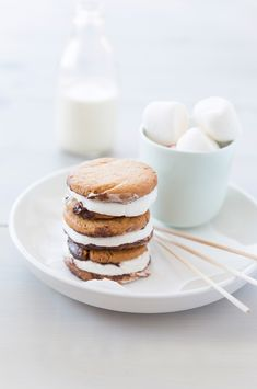 "Recette de smore's (de la contraction de ""so"" et ""more""), deux couches de biscuits, des chamallows et du chocolat que l'on fait traditionnellement cuire au feu de bois"