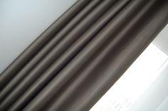Grijsbruine verduisteringsstof met kleine glans en offwhite vitrage in de slaapkamer.