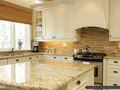 The backsplash in this kitchen created by light, medium, and dark travertine tiles mixes well with the granite countertops and beige cabinets.
