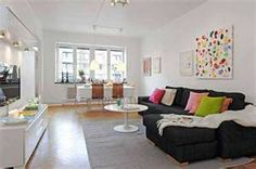Black couches, grey rug, white table/ottoman & tv stand, bright accent pillows