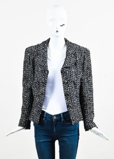 """Classic Chanel jacket from the fall 1997 collection in a black and white tweed. A perfect addition to any wardrobe. Gunmetal buttons with a textured edge and """"CC"""" logo. Rounded, notched lapel. Two fro"""