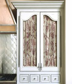 """This is different! """"Cabinet with Fabric Insets in the double doors of this armoire-style kitchen cabinet are a simple and surprising way to create a fine-furniture feel, especially when paired with impressive crown molding and small inset drawers. Another plus? The fabric hides what's stored behind--anything from bulky pots and pans to canned goods."""""""