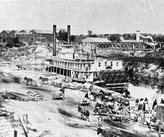 Black and white photograph of St. Claire paddleboat at Allen's Landing. S.L. Allen Company building can be seen in the background. In the foreground near the water and paddleboat are horses with wagons and men working. #AllensLanding #HoustonHistory #BuffaloBayou #Houston #History