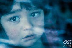 Niño mirando atreves de una ventana de vidrio a la cámara