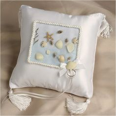 WeddingDepot.com ~ Ring Bearer Pillow - Seaside Beach Wedding Pillow ~ Soft white matte satin provides the perfect background for the collection of seashells that adorn the top of the pillow. Arranged on a light sea blue palette, the shells are surrounded by white cording similar in style to the ropes you see near the seashores.