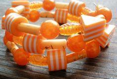 Veselý náramok s rôznymi kúskami plastových korálok a perlí na pamäťovom drôte. Orange