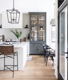 This photo from @ldshoppe really showcases the kitchen hutch. Adding in the deep grey really breaks up the mainly white palette through the kitchen and the wood inlay warms things up and ties back into the floors. It's nearly 10 feet tall - I'm on the search for a stylish ladder to get up there! If you have a ladder recommendation, shout it out! . . . Photo/Furnishings: @ldshoppe Interior Design: @ten_and_co . . . #modernfarmhouse #modernfarmhousestyle #modernfarmhousekitchen #farmhousestyle #