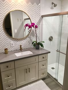 Small bathroom remodel. Grey and white chevron partial backsplash, hexa shower tile, gold faucet, gold round mirror, polished brass fixtures, gray wood tile floor, cream cabinet.
