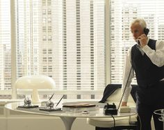 Roger Sterling's minimalist office pairs the now-classic Saarinen Tulip table with an Artemide Nesso table lamp.