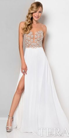Be one in a million in the Illusion Beaded Thigh Slit Prom Dress by Terani Couture. This sweet and stylish number features an illusion neckline and a low illusion back with a zipper down the center. The straight silhouette includes a sleeveless bodice with beautiful beaded clusters and a thigh high slit with a sweep train. #edressme