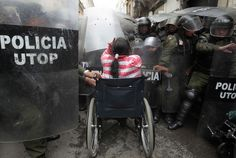 A physically disabled woman in her wheelchair clashes with riot police in the center of La Paz, Bolivia.