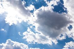 white clouds blue sky fluffy sun flare airplane trail sunny daytime