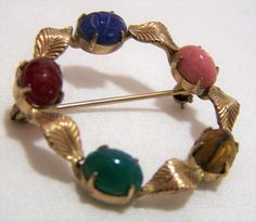 Vintage Mid Century WRE round scarab brooch with leaf design Scarabs are carnelian, chalcedony, rhodonite, tigers eye and chrysoprase WRE is the WE Richards Jewelry Co. My personal favorite Signed WRE 1/20 12k gf 1 3/8 inches diameter Scarabs are 8 x 6 mm Very good vintage condition, shows no wear I specialize in vintage scarab jewelry, please visit my shop for more selections International buyers welcome, overcharges are refunded Flat rate Priority shipping is optional  Credit card...