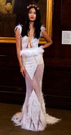 Vestido de noiva Berta Bridal desfilados na NY Bridal Week com recortes e transparências. Moderno, justo ao corpo e com penas na cintura, saia e manga.