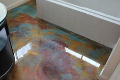 Paint the concrete, the add colorants to epoxy and swirl $5/sq ft: Concrete Floor Ideas | Concrete Floor Finishes | Flooring Tips