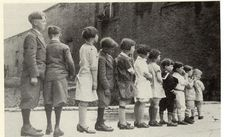 From the 1850s up through the 1920s, abandoned or homeless children in New York City were uprooted and put on trains that took them to rural communities. Here several children are lined up with the hopes that someone will take them to a new home.